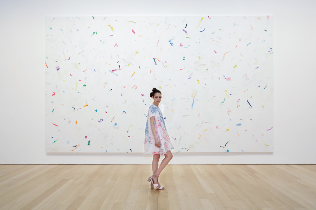 Paridust in front of a confetti painting by Dan Colen, at The Brant Foundation, Greenwich, Connecticut, wearing Tanya Taylor.  Photograph by Tylor Hou, 2014
