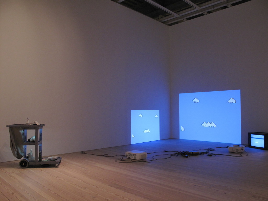 Josh Kline (left), Cost of Living (Aleyda), Plaster, ink, and cyanoacrylate: janitor cart: and LEDs, 2014, Cory Arcangel (right), Super Mario Clouds, Handmade hacked Super Mario Brothers cartridge and Nintendo NEW video game system Edition no. 2/5, 2002, Whitney Museum of American Art, Photograph by Katy Hamer, 2015